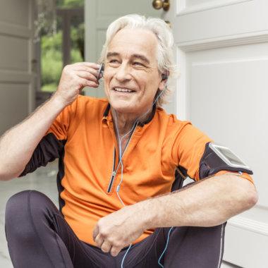 Senior male runner at front door preparing earphone music