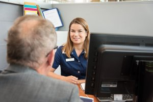 Docrates Syöpäsairaalan koordinoiva hoitaja Katri juttelee miespotilaan kanssa